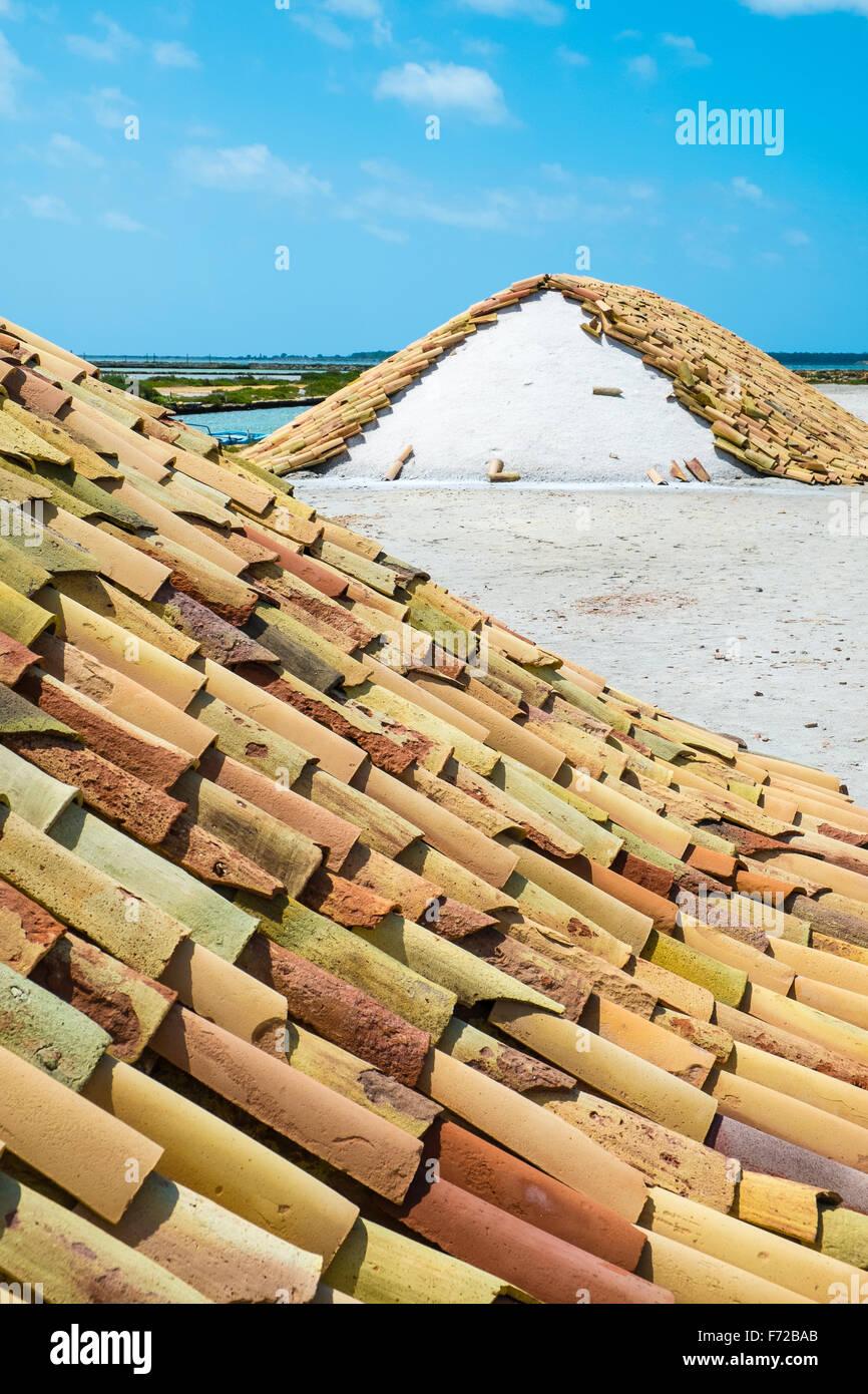 La sal cosechada desde el mar en Trapani, Sicilia se almacena en montones en azulejos de terracota, esperando el Imagen De Stock
