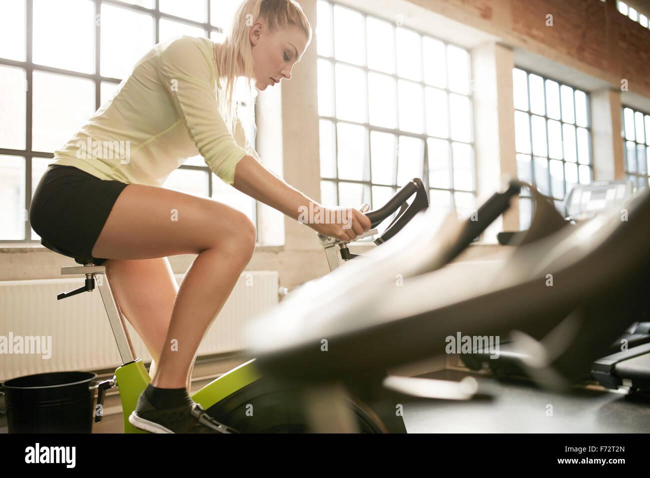 Colocar una mujer trabajando en bicicleta de ejercicio en el gimnasio. Centrado las hembras jóvenes de ejercicio Imagen De Stock