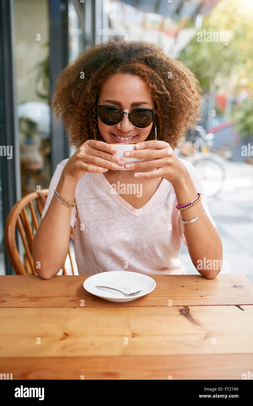 Retrato de joven africana bebiendo café en el café en la acera. Atractiva chica con el pelo rizado sosteniendo Imagen De Stock