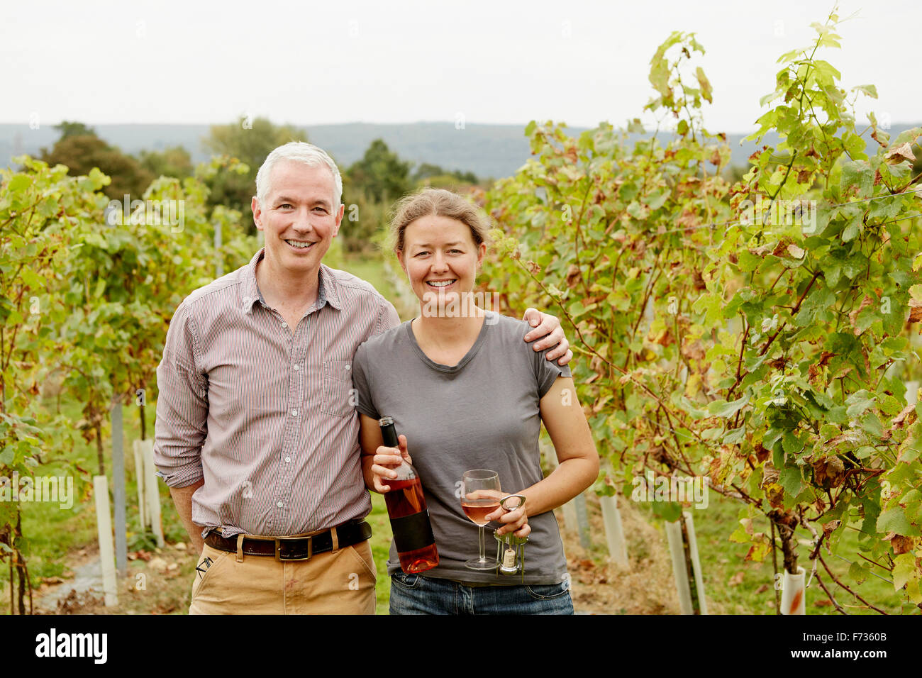 Una pareja, viñedo y su socio fundador de pie entre las hileras de vides. Imagen De Stock
