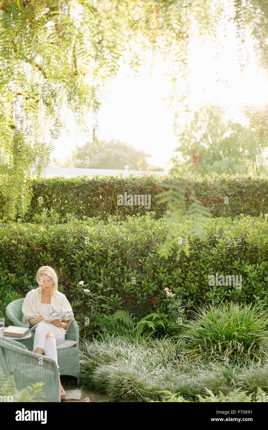 Mujer rubia sentada en una silla de mimbre en un jardín. Imagen De Stock