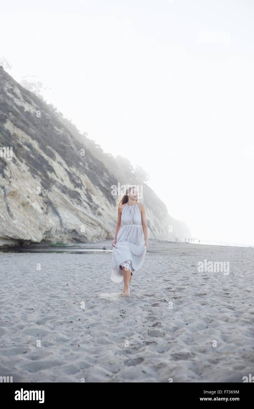 Mujer rubia caminando en una playa de arena, cerca de un acantilado. Imagen De Stock