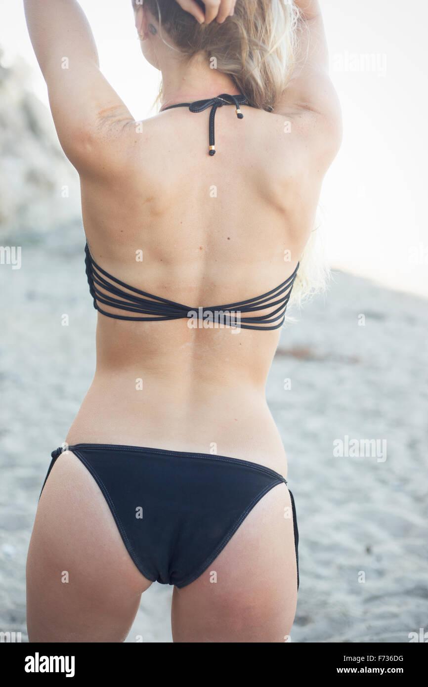 Mujer rubia en un bikini negro en una playa de arena. Imagen De Stock