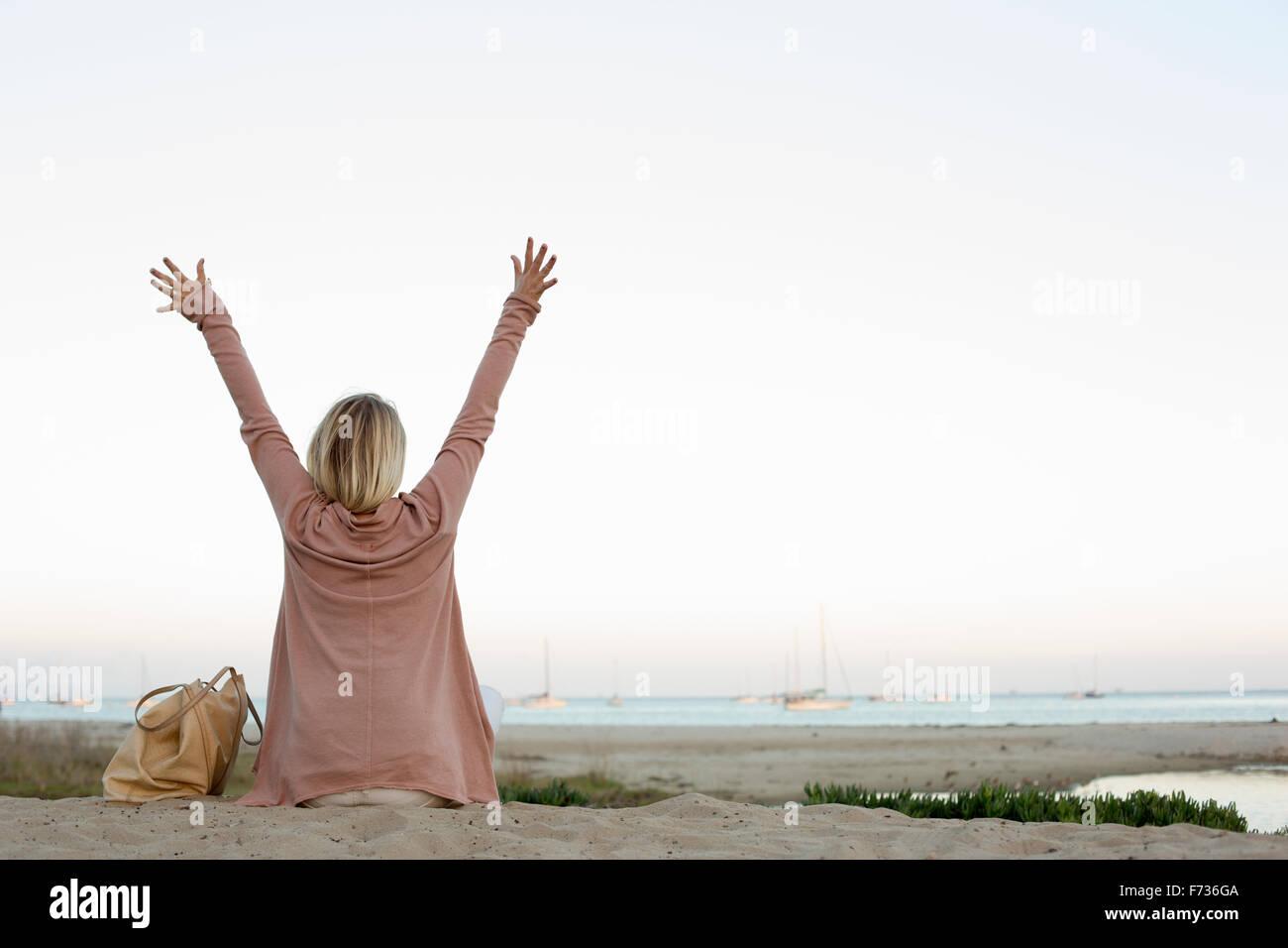 Mujer rubia sentada en una playa de arena, con los brazos en alto. Imagen De Stock