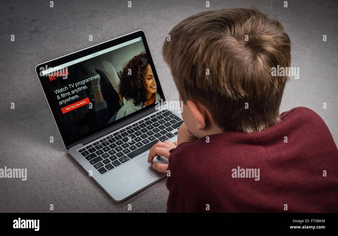 Un niño ve Netflix en un ordenador portátil Imagen De Stock