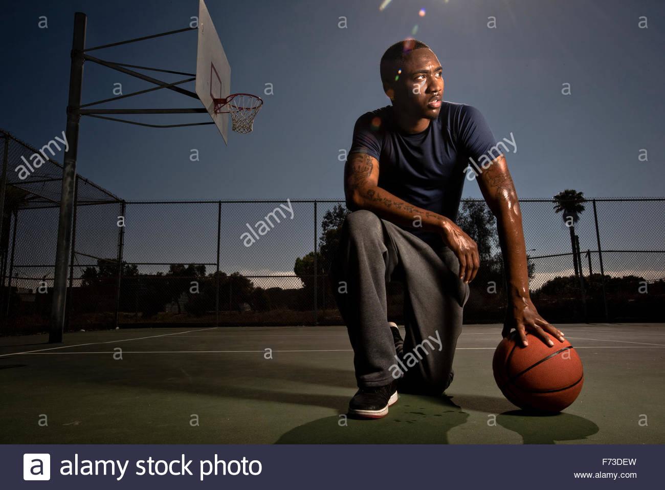 Un jugador de baloncesto jugador descansa en el tribunal después de un juego. Imagen De Stock