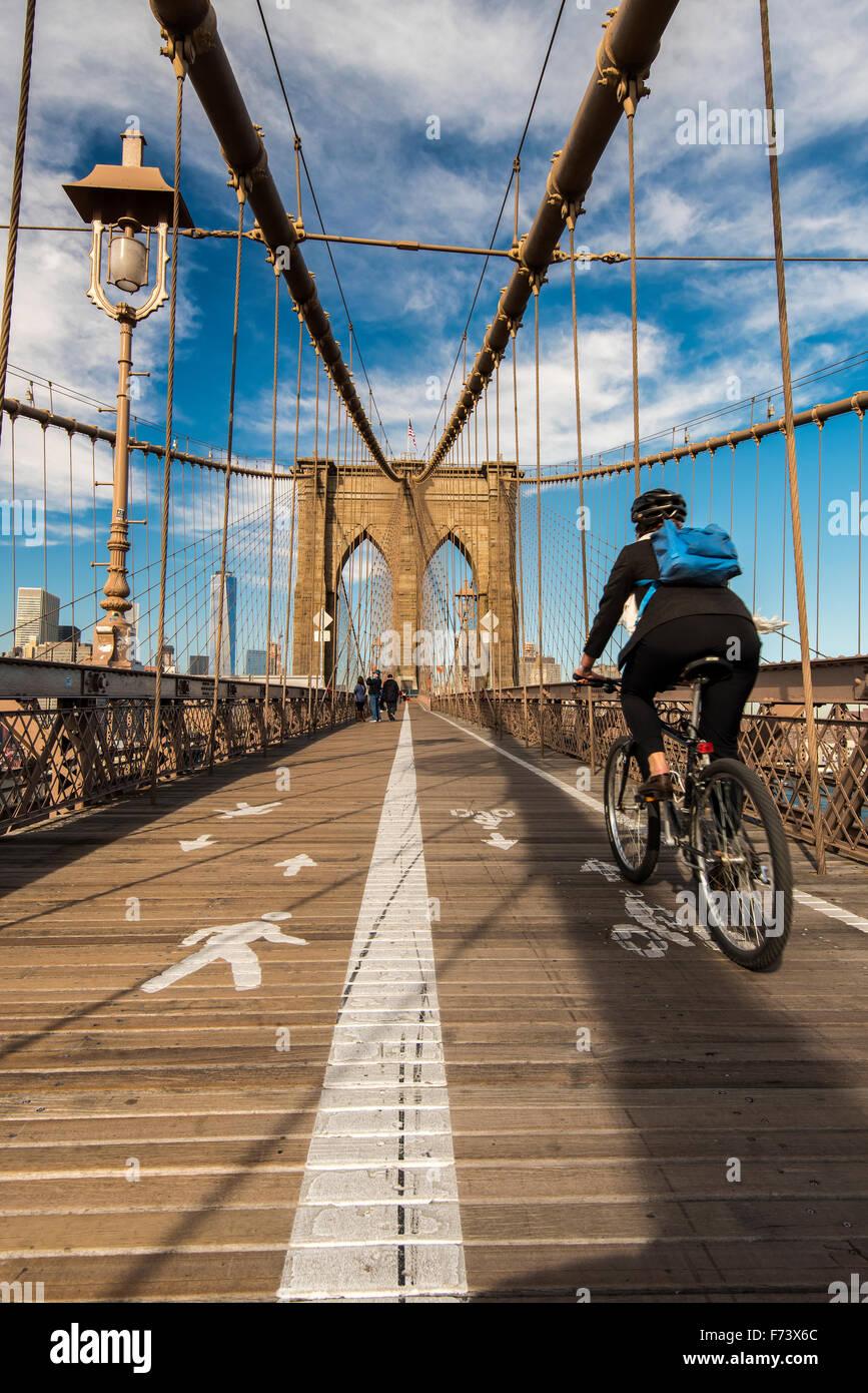Su bicicleta Equitación ciclista sobre el puente de Brooklyn, Nueva York, EE.UU. Imagen De Stock
