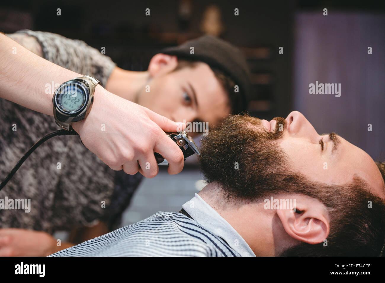 Atractivo hombre barbado obteniendo su barba afeitada por modernos barber Barber shop Foto de stock