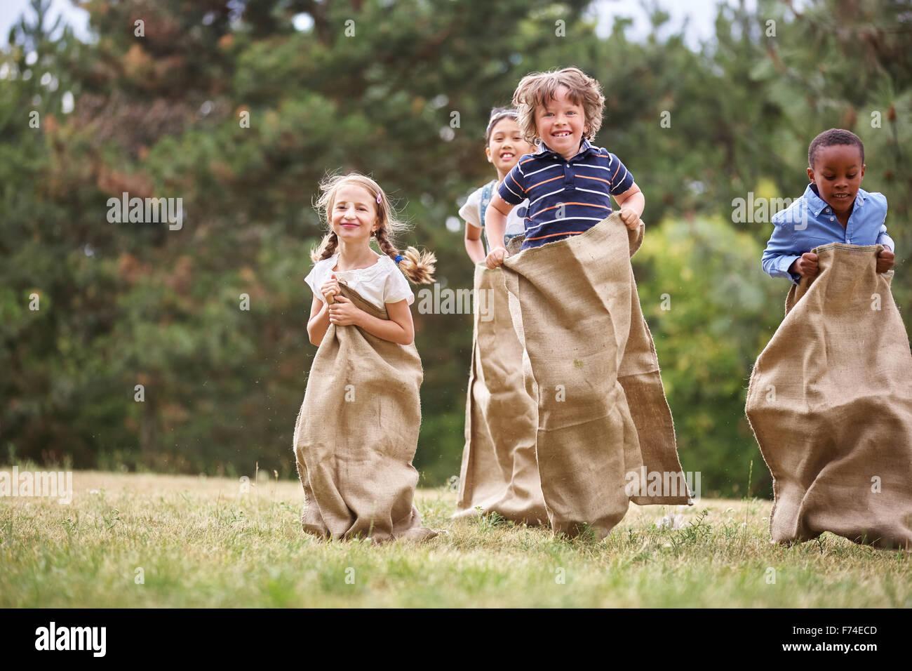 Interracial grupo de chicos con futón en carrera de sacos Imagen De Stock