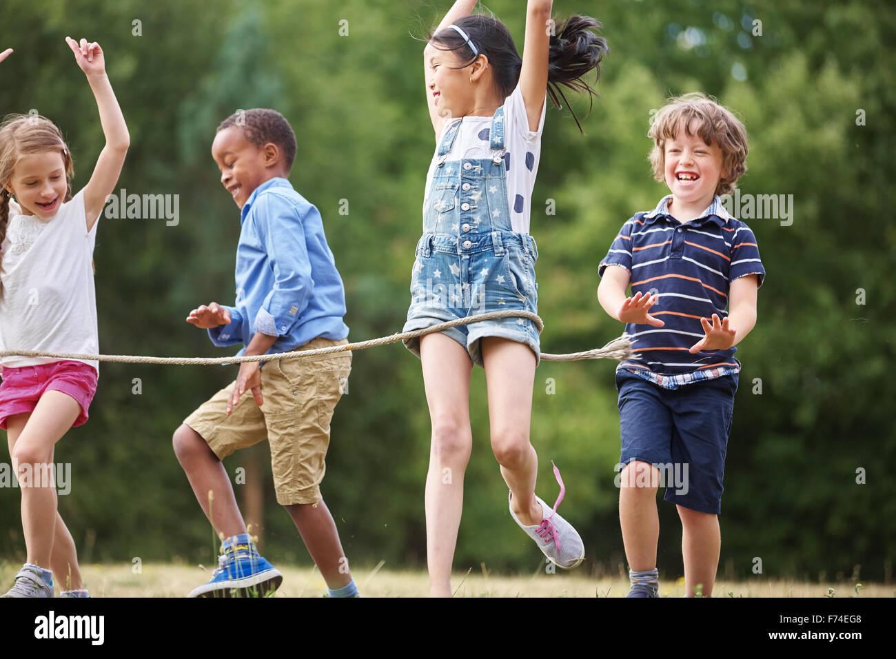 Interracial grupo de niños llegar a la línea de meta en una carrera amistosa Foto de stock