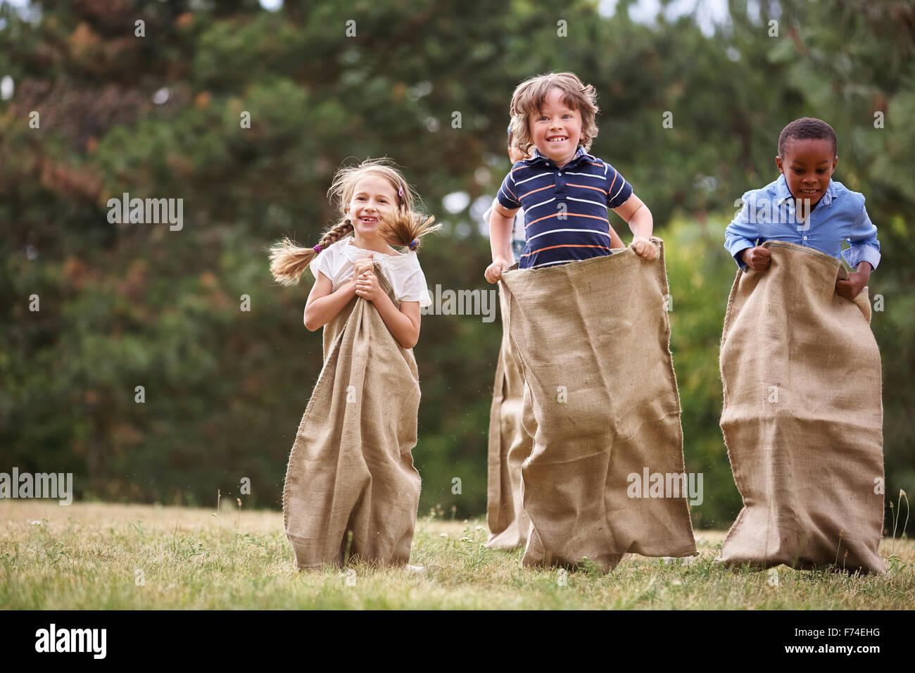 Los niños compiten en carrera de sacos y divertirse Imagen De Stock