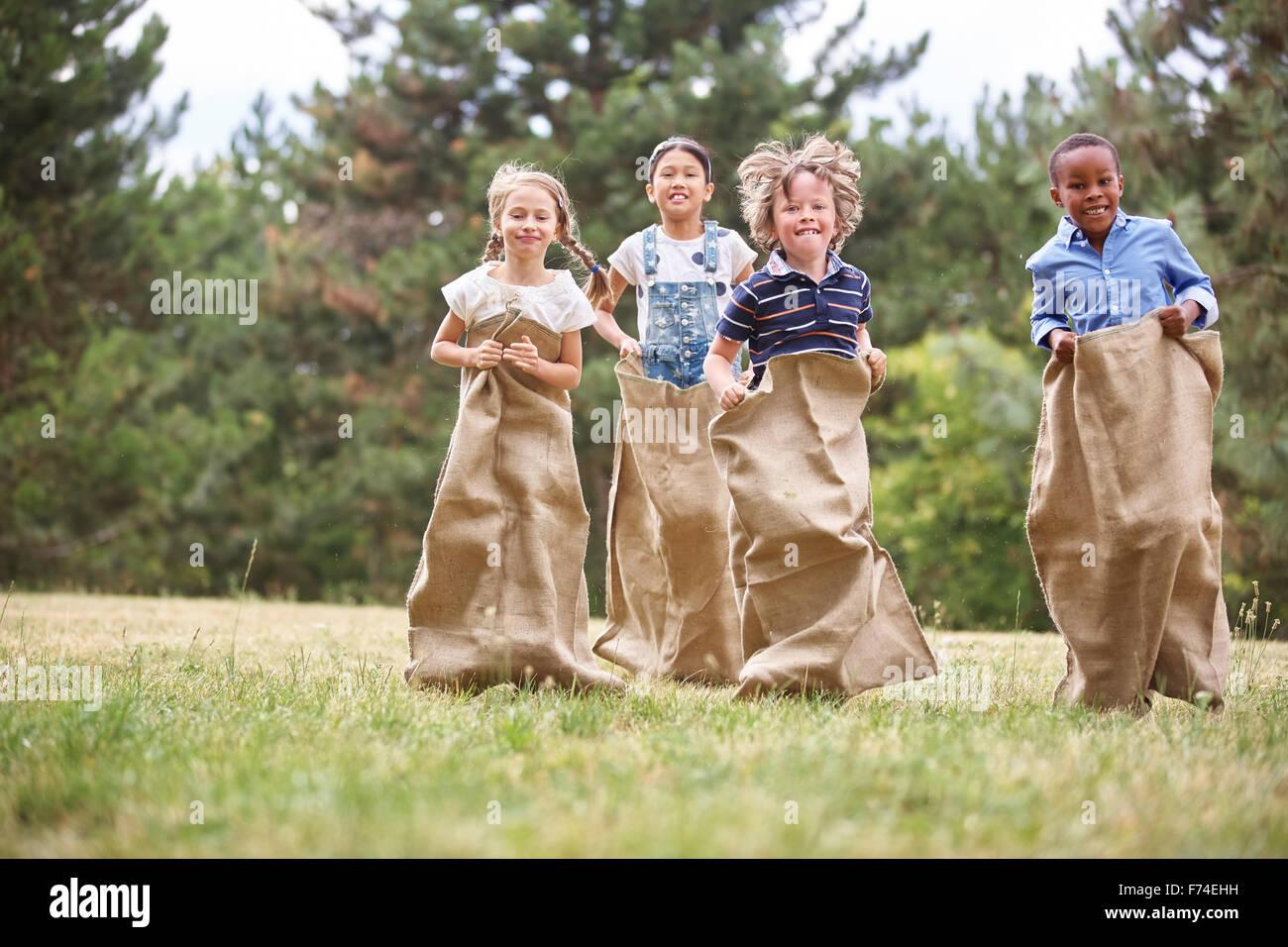 Los niños se diviertan en carrera de sacos en el parque Imagen De Stock