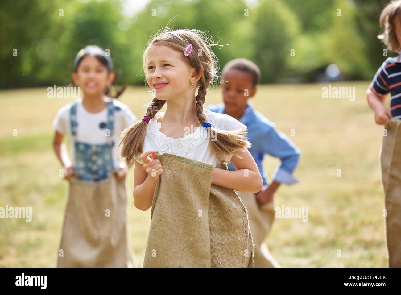 Chica con cabello trenzado en carrera de sacos en el parque Imagen De Stock