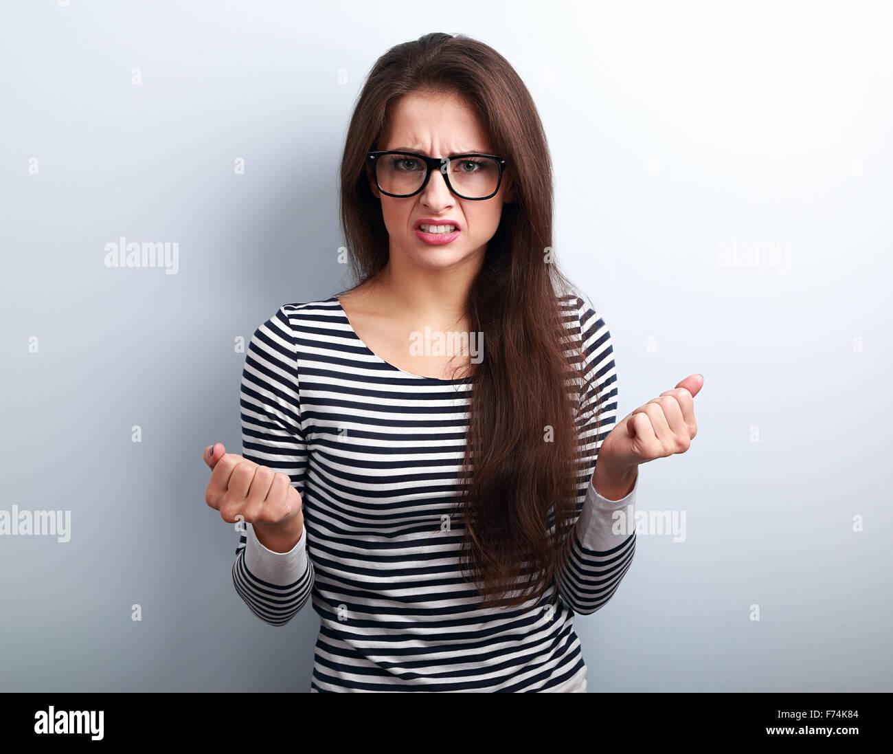 Enojado nervioso joven en gafas con cara negativa agresiva mostrando puños sobre fondo azul. Imagen De Stock