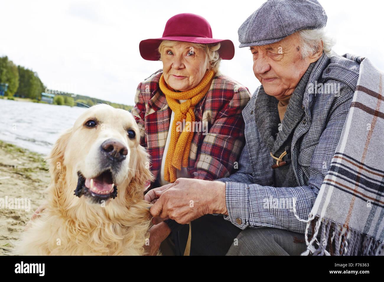 Pareja de jubilados y su mascota disfruta de descanso de fin de semana por la costa Imagen De Stock