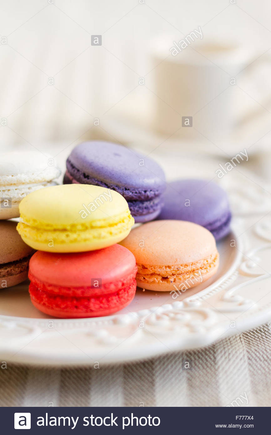 Macarons de diferentes colores en blanco retro plato. Enfoque selectivo Imagen De Stock