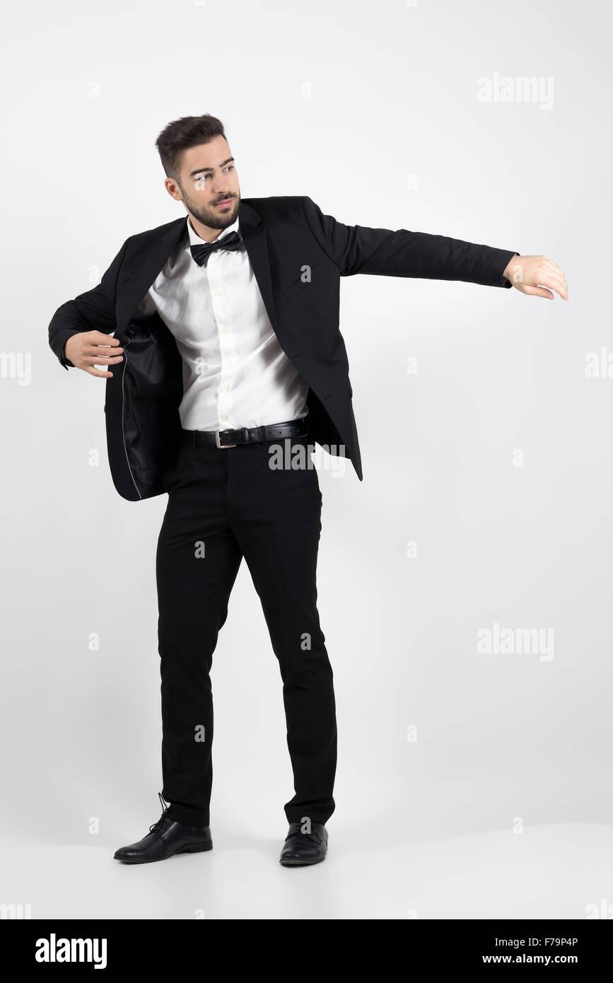 Joven poniendo en traje negro esmoquin que cubra. Longitud de cuerpo  completo retrato sobre fondo gris studio f88d974dc32