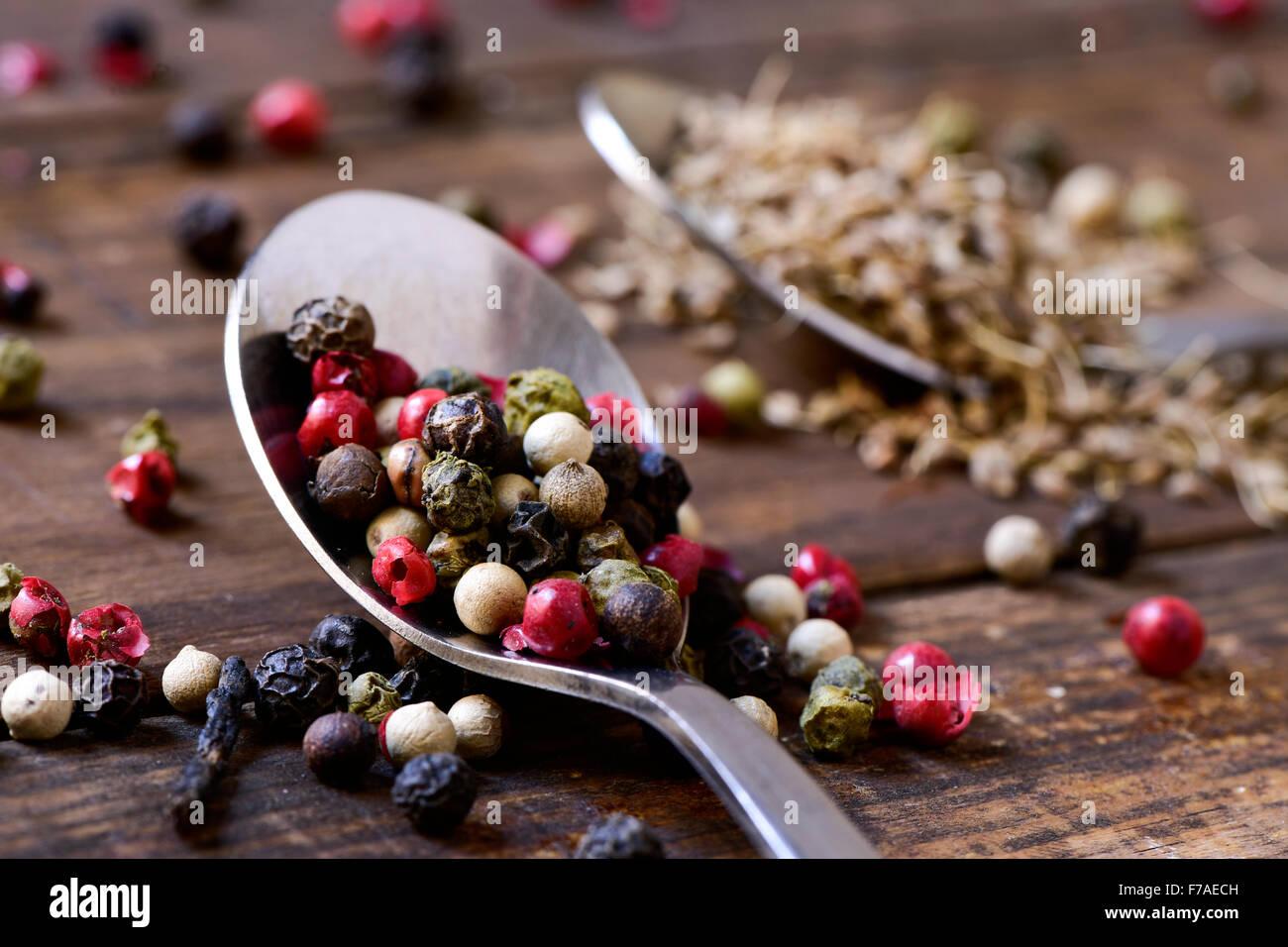 Primer plano de una cuchara con una gran variedad de granos de pimienta, tales como la pimienta rosa, pimienta negra, Foto de stock