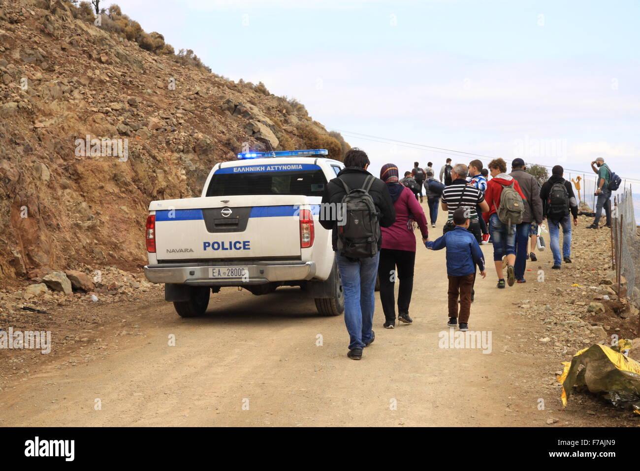 Los refugiados e inmigrantes de la familia llegan escoltados por la policía en Molyvos en la isla de Lesbos en Grecia Foto de stock