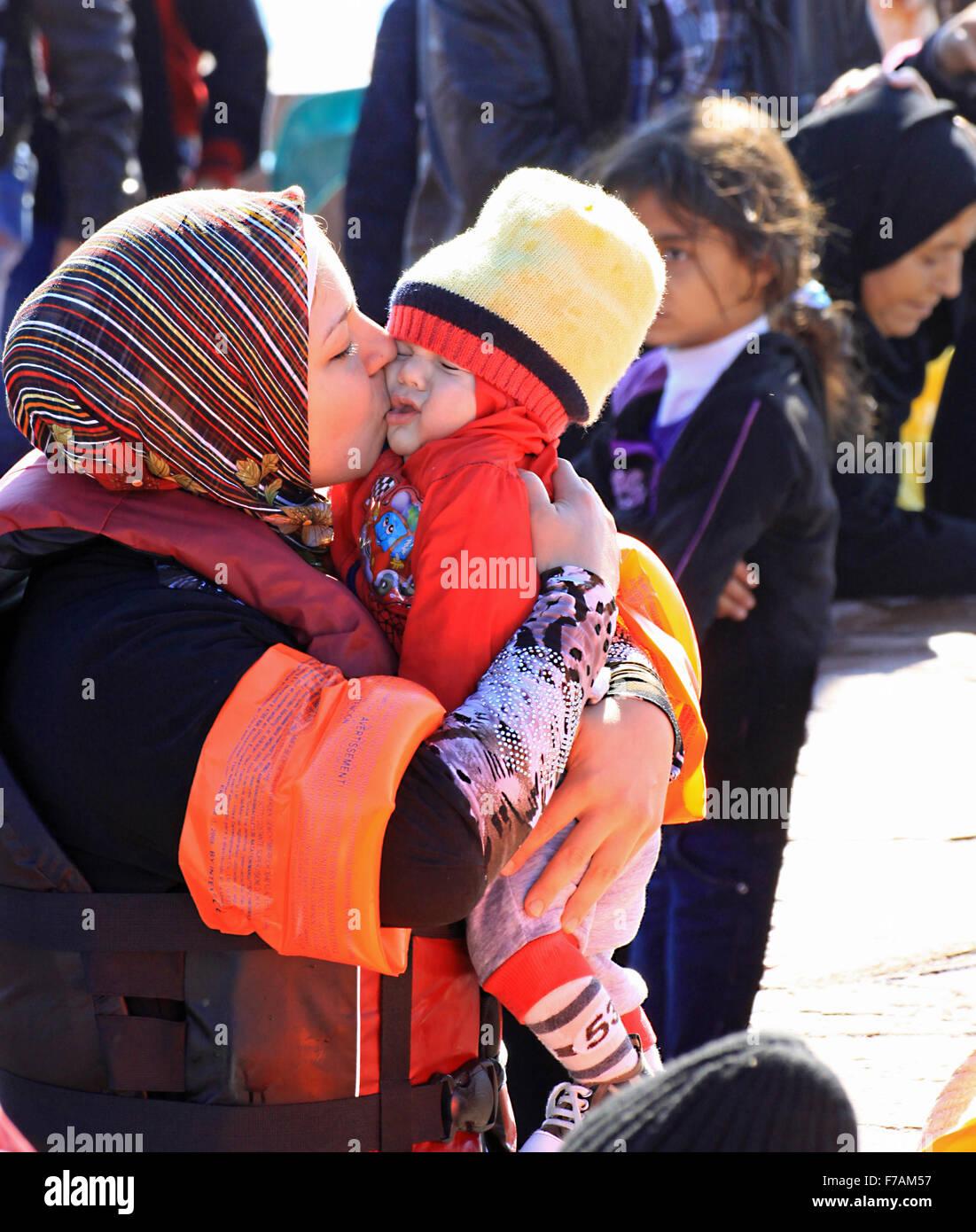 Los refugiados e inmigrantes llegan a la familia Molyvos en la isla de Lesbos en Grecia después de huir de la guerra Foto de stock