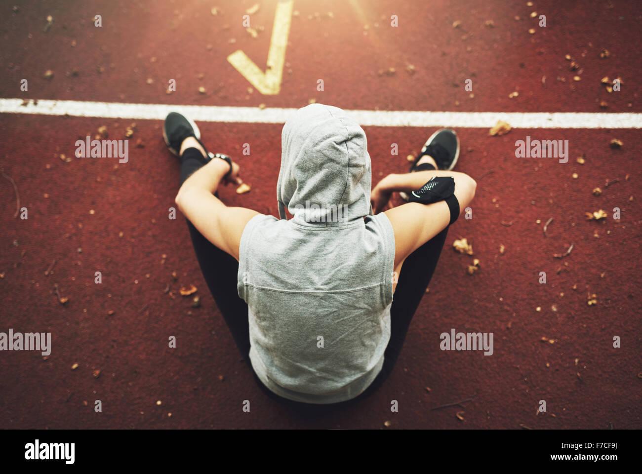 Vista posterior de la mujer joven en ropa deportiva sentado en campo track y preparación antes de la formación.irreconocible Foto de stock