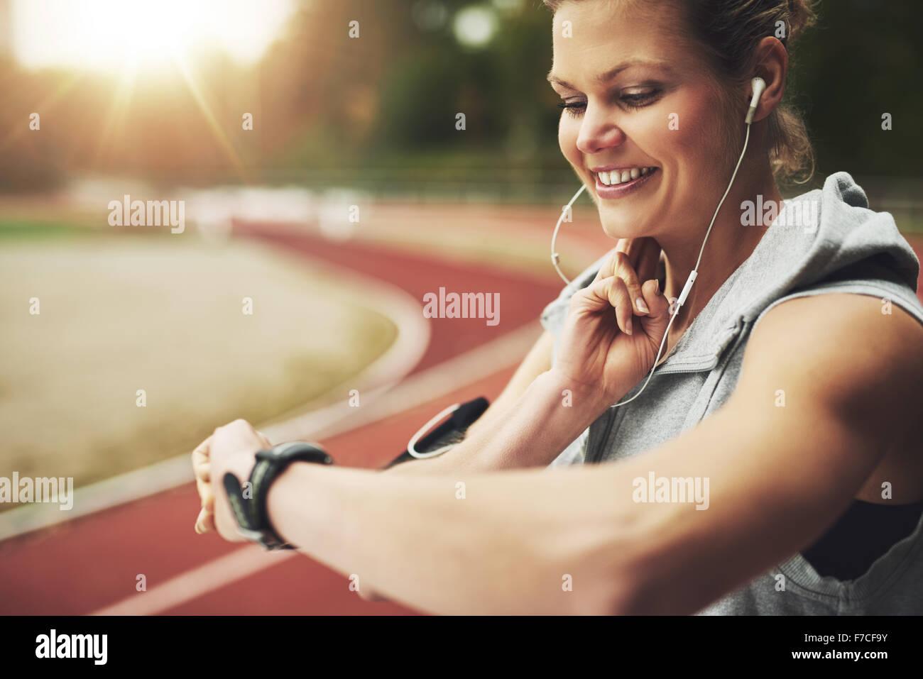 Close-up smiling sportswoman mirando su reloj y sintiendo el pulso en la pista antes del entrenamiento de campo Foto de stock