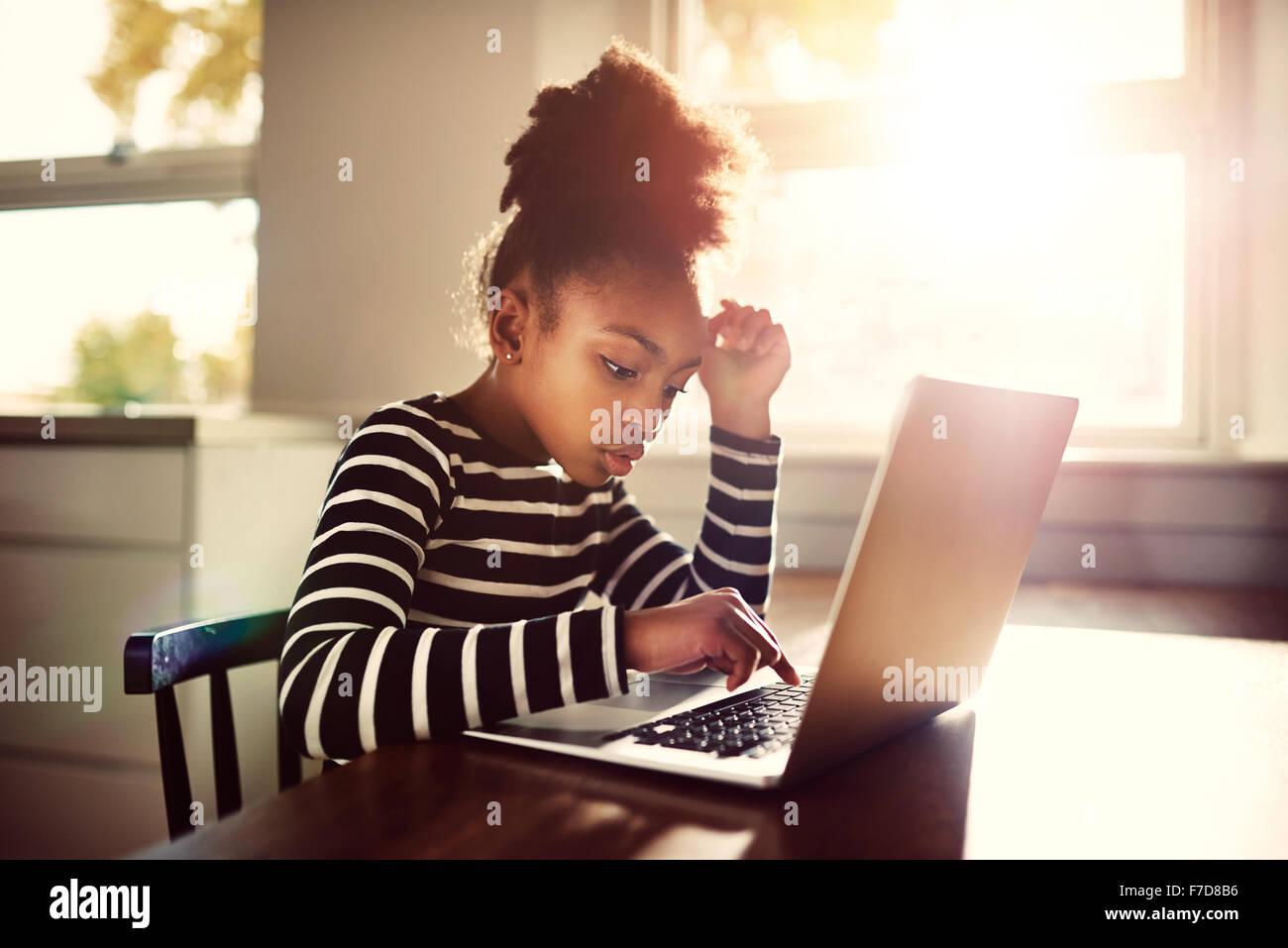 Niña sentada en la mesa del comedor en casa trabajando en sus deberes de la escuela de escribir una respuesta en Foto de stock