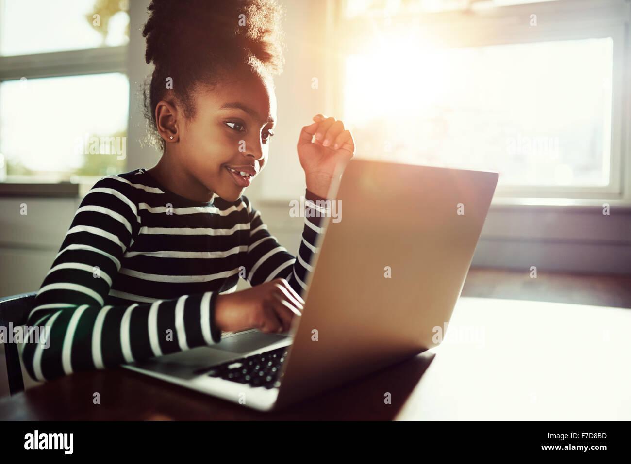 Poco étnicos en casa chica sentada en una mesa trabajando en sus deberes en un ordenador portátil que Imagen De Stock