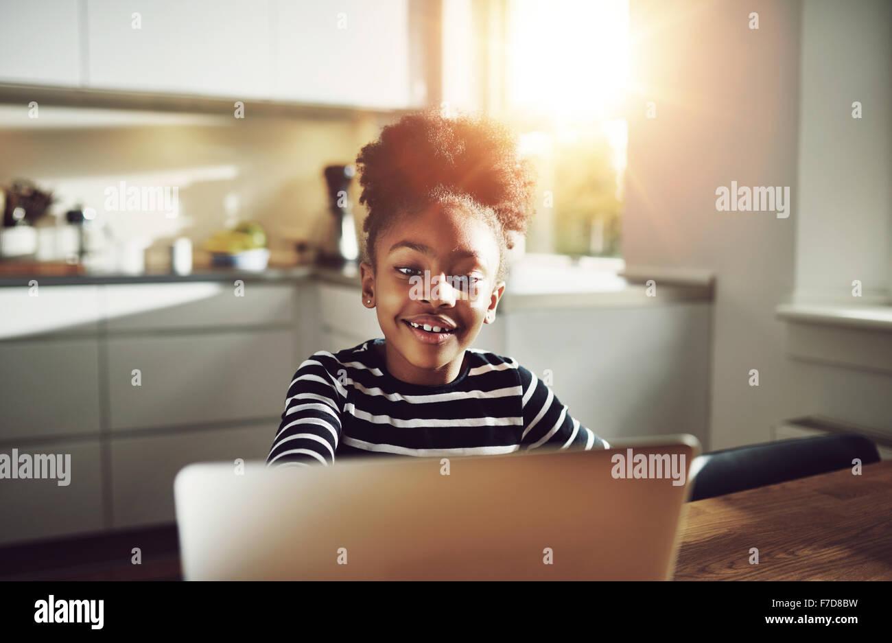 Lindo joven negro niña jugando en un equipo portátil sonriendo felizmente ella navega por internet mientras Imagen De Stock
