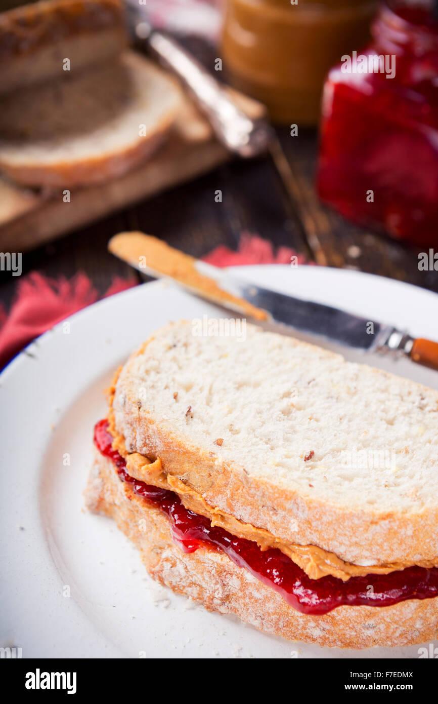 Cierre de un sándwich de mantequilla de maní y mermelada en una mesa de estilo rústico. Imagen De Stock
