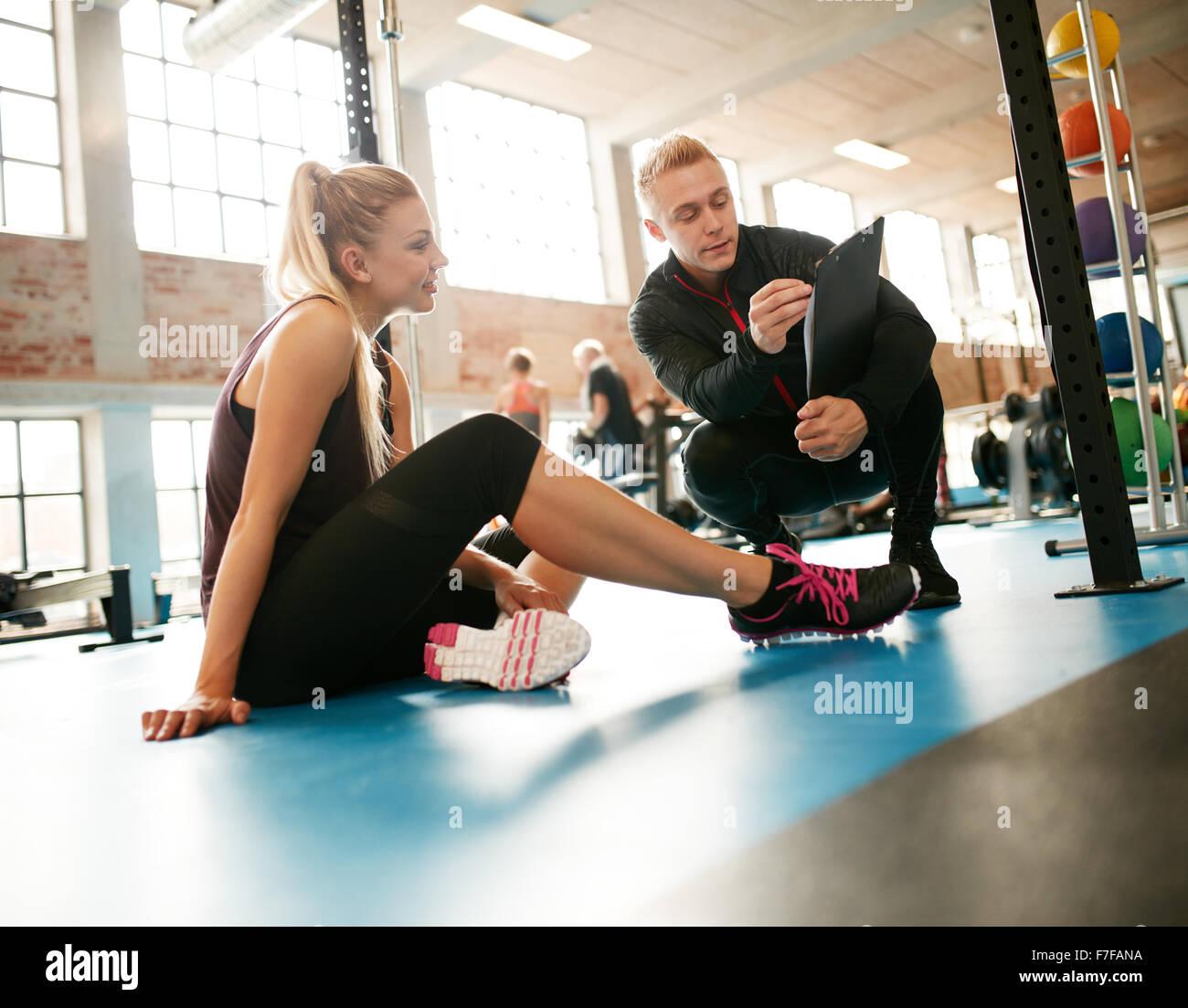 Entrenador personal joven ayudando en su labor fuera rutinas en el gimnasio. Mujer sentada en el suelo con su personal Imagen De Stock