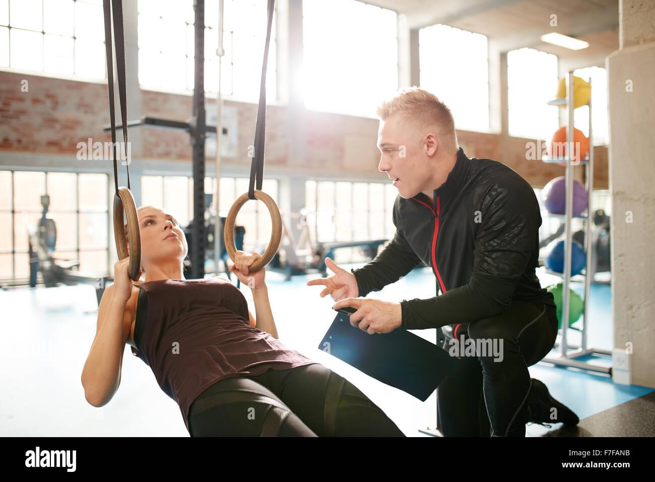 Instructor masculino ayudando a una joven mujer durante una sesión de entrenamiento en el gimnasio en los anillos. Imagen De Stock