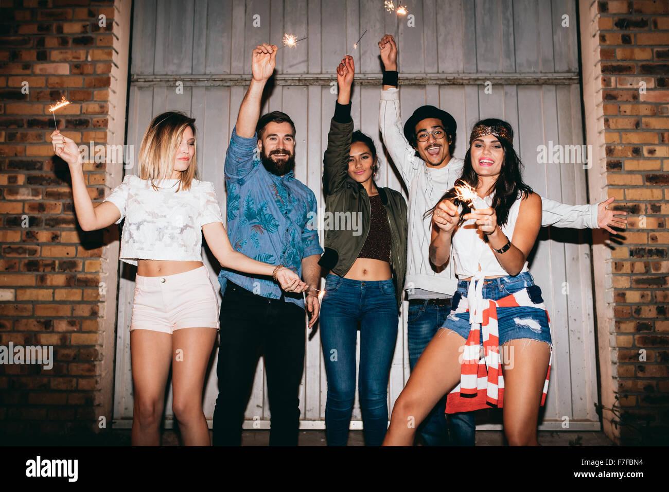 Los jóvenes feliz por la noche, celebrando con estrellitas. Jóvenes amigos, una fiesta al aire libre. Imagen De Stock