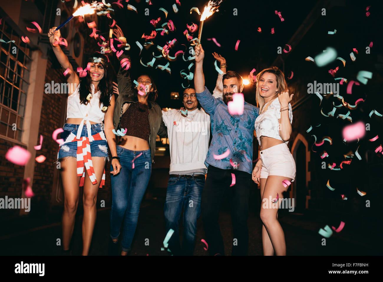 Grupo de jóvenes en una fiesta, al aire libre. Hombres y mujeres jóvenes multirracial celebrando con confeti. Imagen De Stock