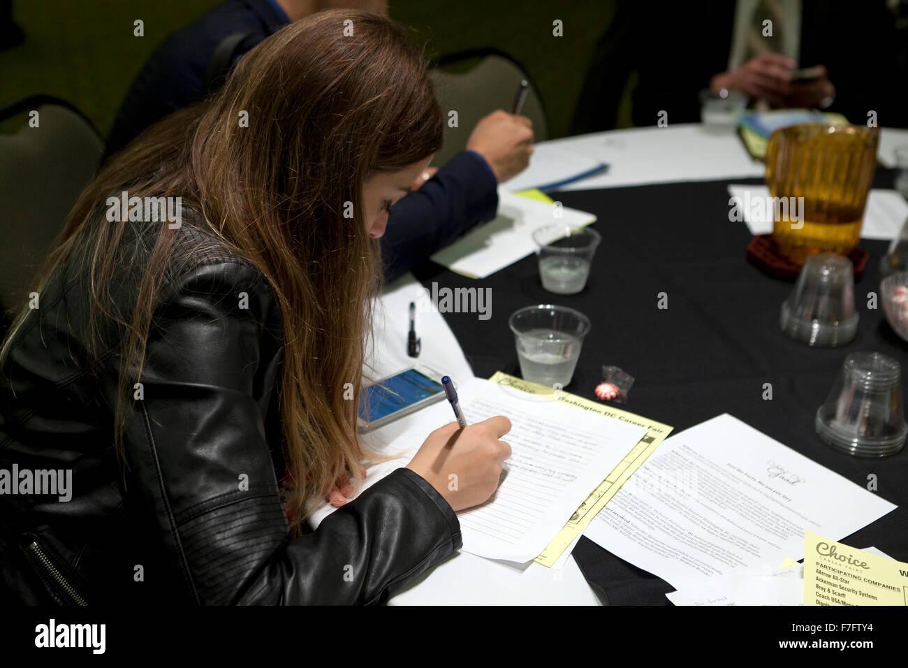Mujer joven rellenando una solicitud en la contratación justos - Arlington, Virginia, EE.UU. Imagen De Stock