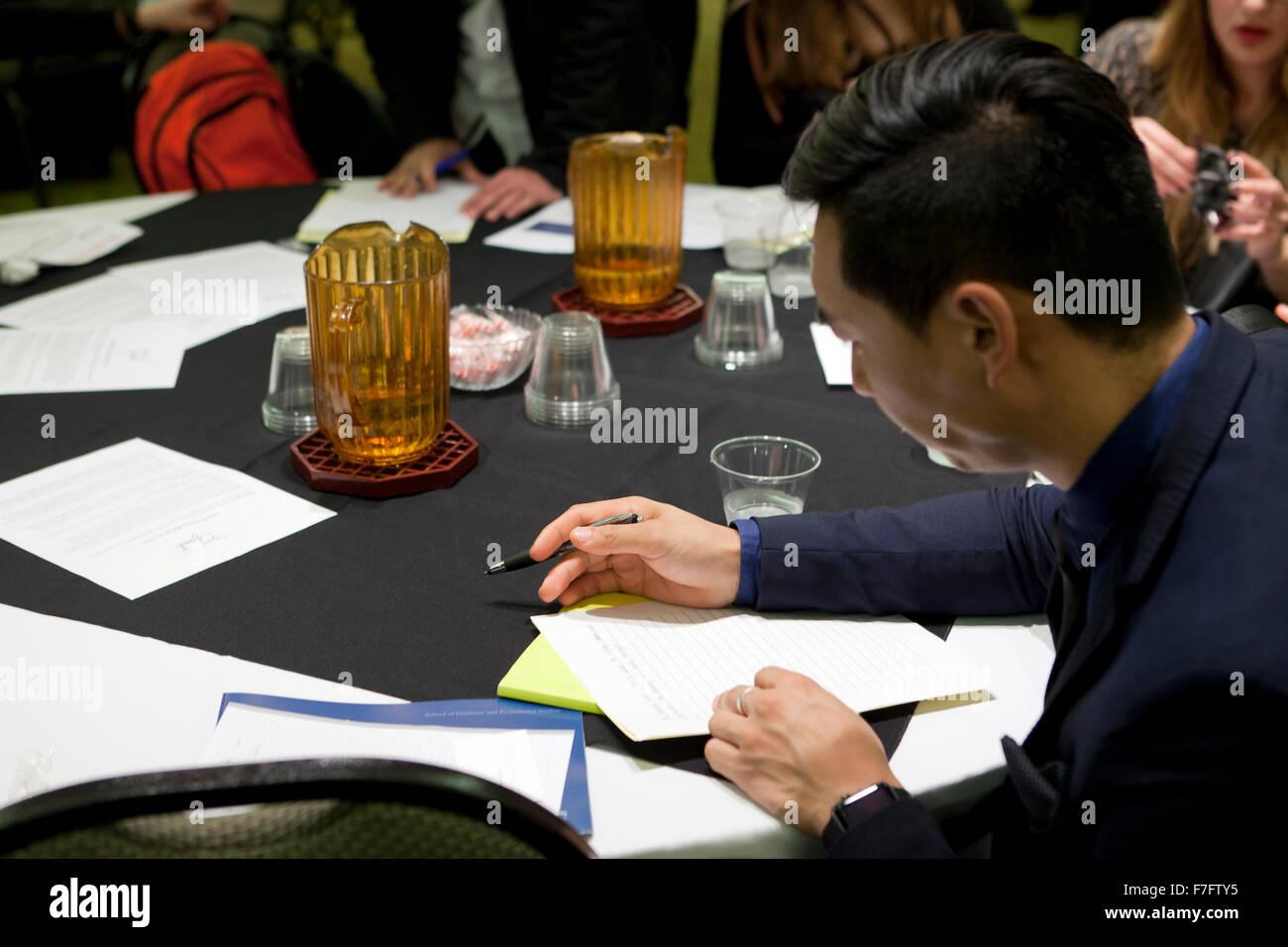 Joven hombre asiático rellenando una solicitud en la contratación justos - Arlington, Virginia, EE.UU. Imagen De Stock