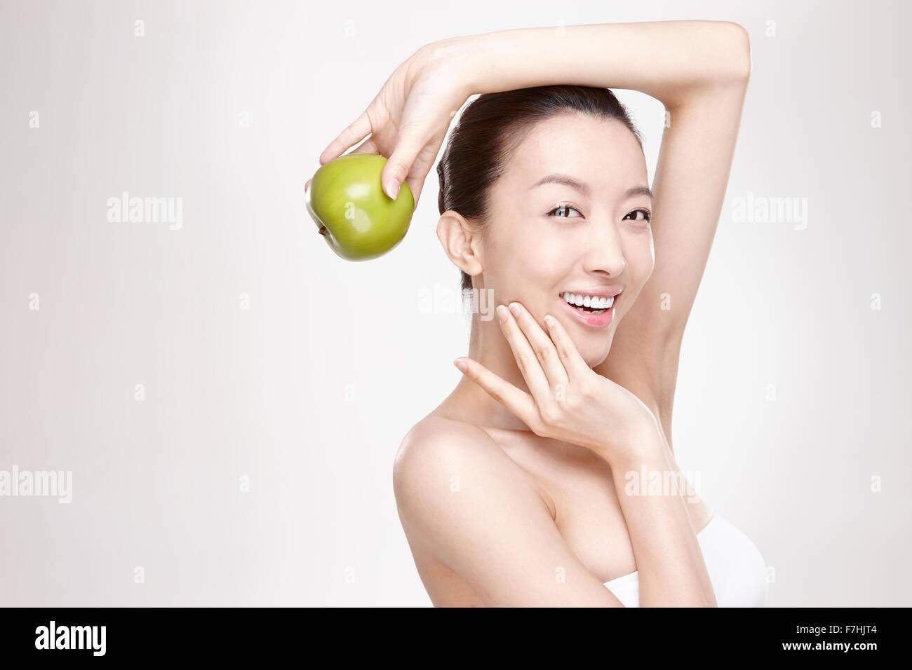 Mujer sonriente sosteniendo una manzana verde Imagen De Stock