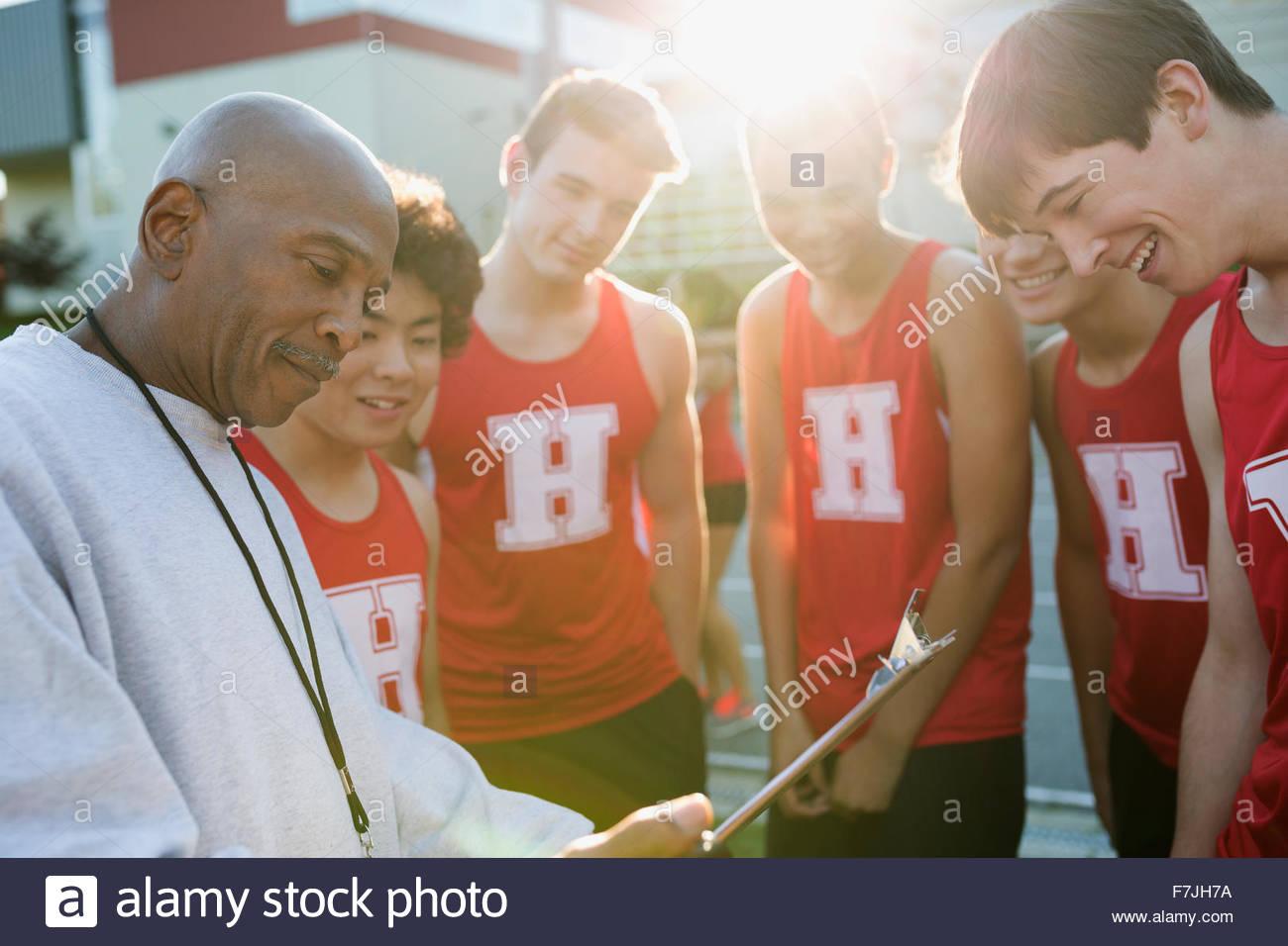 Entrenador con el portapapeles hablando con atletas de secundaria Imagen De Stock