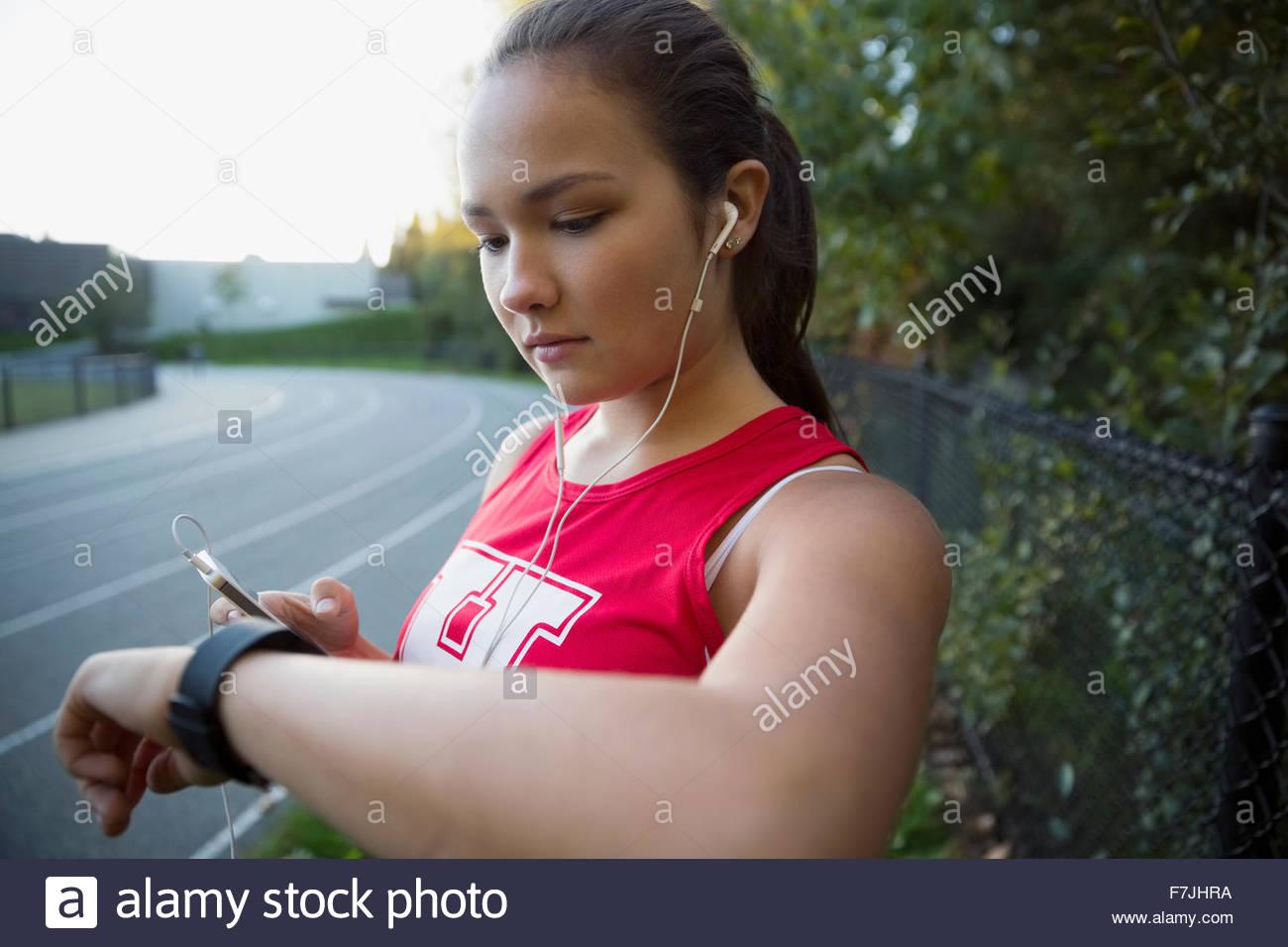 High school atleta escuchando música control reloj de pulsera Imagen De Stock