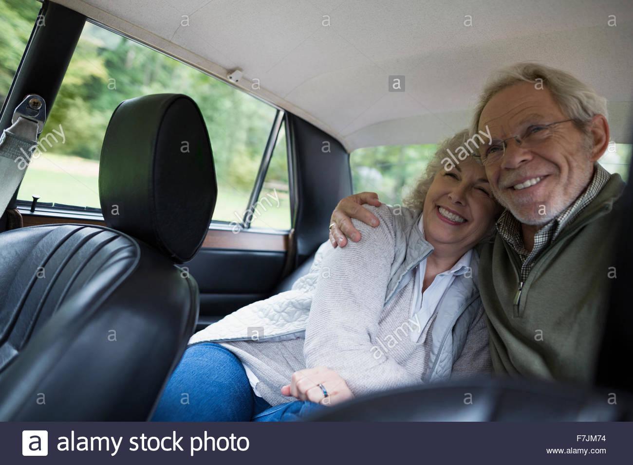 Las parejas ancianas abrazarse y sonriente asiento posterior coche Imagen De Stock