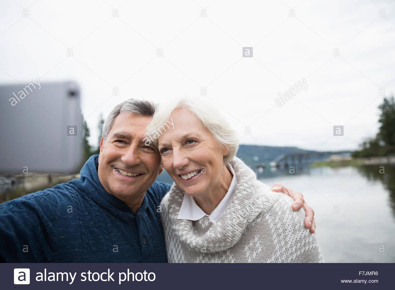 Las parejas ancianas teniendo selfie con el lago en segundo plano. Imagen De Stock