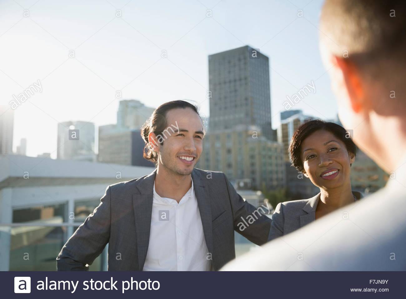 Personas hablando de negocios en la soleada azotea urbana Imagen De Stock