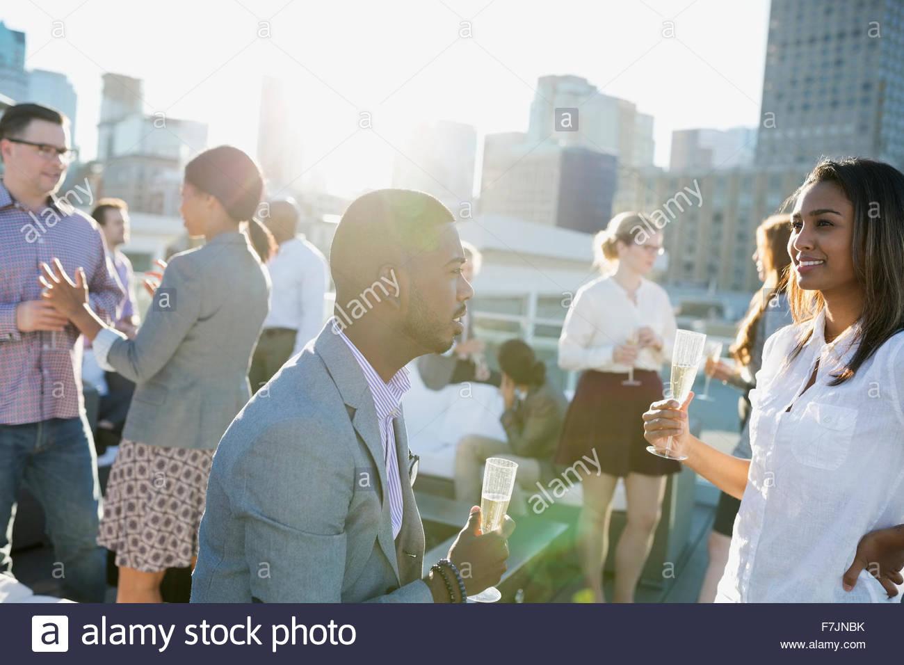 Gente de negocios beber champán socializar en la soleada azotea Imagen De Stock