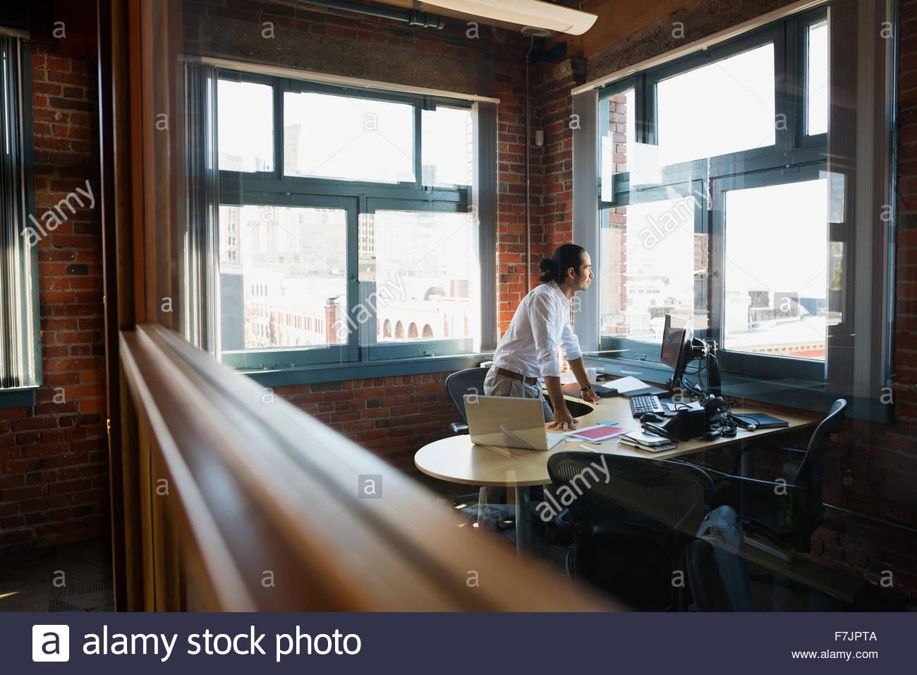 Empresario pensativo mirando la ventana de oficina Imagen De Stock
