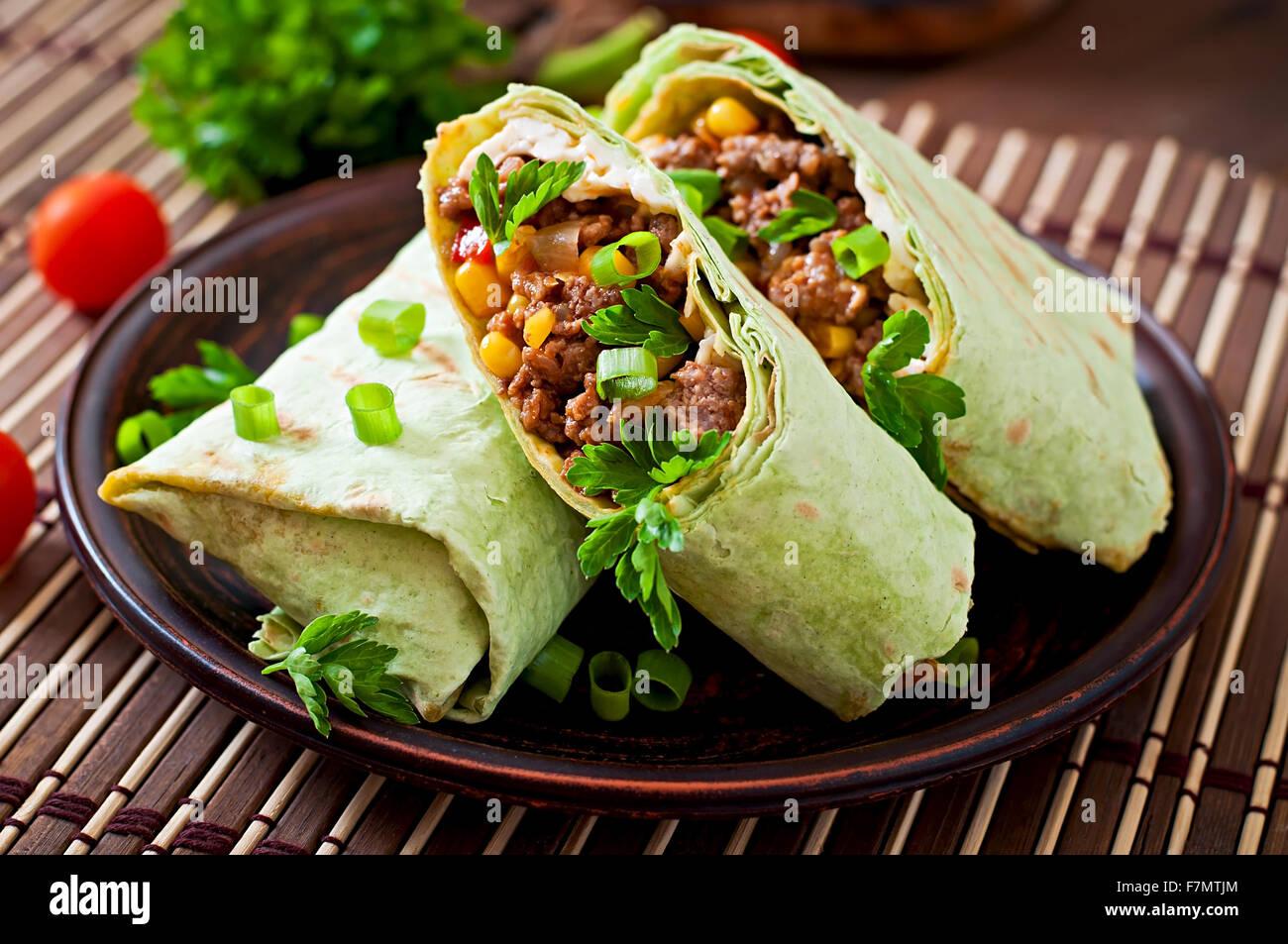 Los burritos envuelve con carne picada y verduras sobre un fondo de madera Imagen De Stock