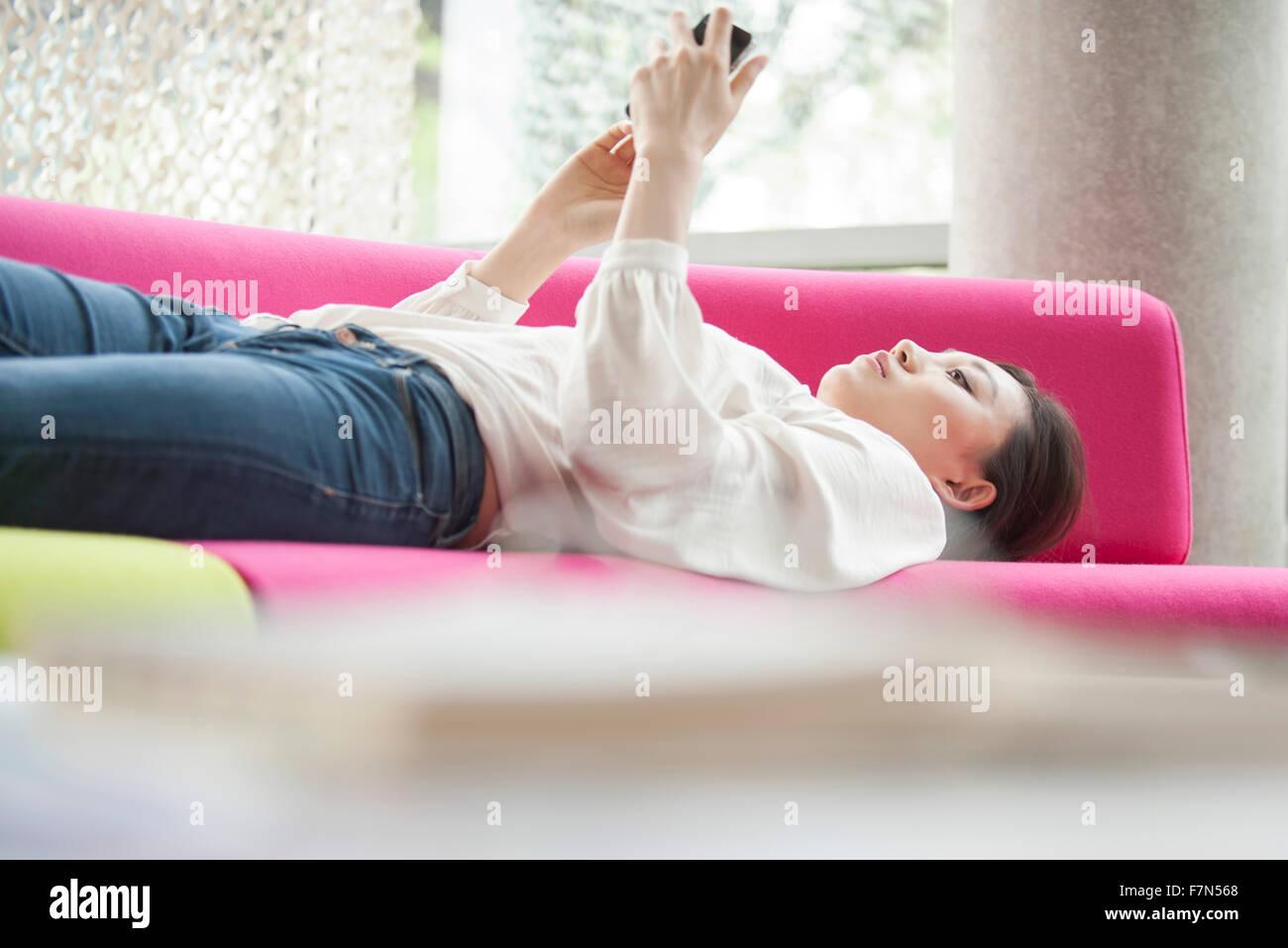Mujer viendo vídeos en el smartphone en casa Foto de stock