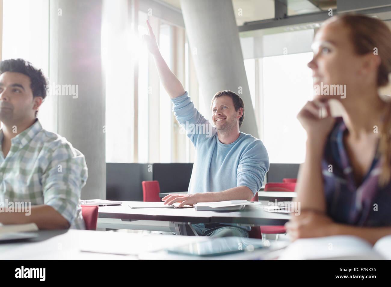 Impaciente hombre levantando la mano en el aula de educación de adultos Imagen De Stock