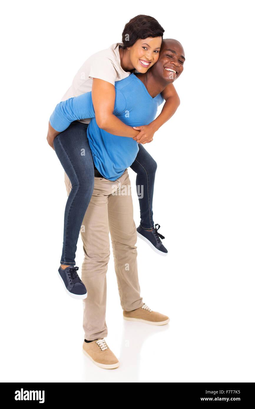 Juguetón pareja americana africana piggyback sobre fondo blanco. Imagen De Stock