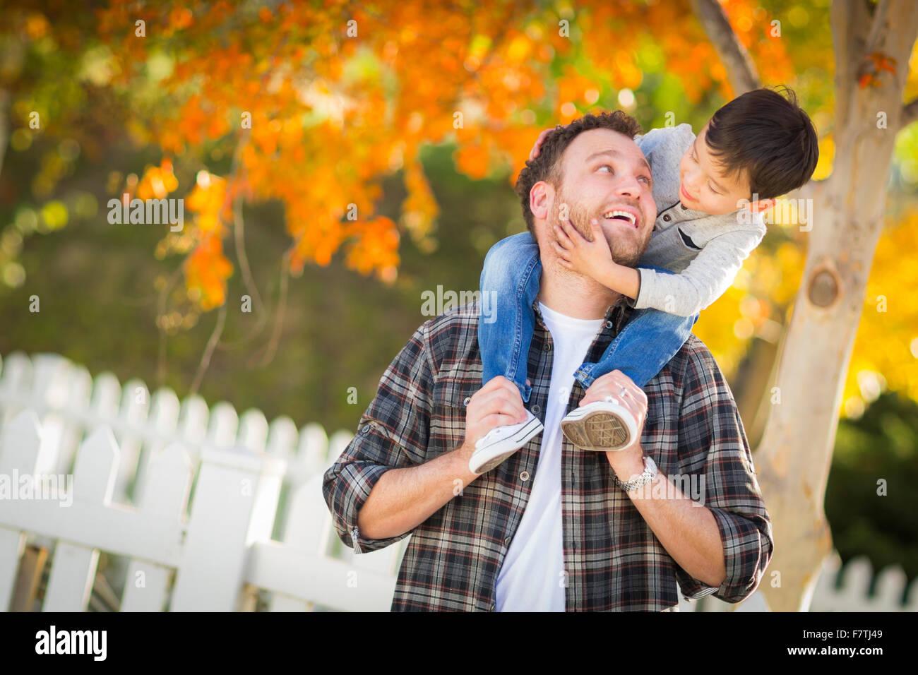 Feliz Mestizos Boy Caballo Piggyback sobre los hombros del Padre caucásico. Imagen De Stock