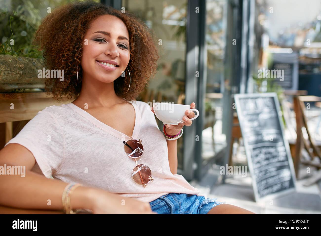 Retrato de mujer joven bebiendo café. Mujer Africana sentado en el cafe sosteniendo una taza de café, Imagen De Stock